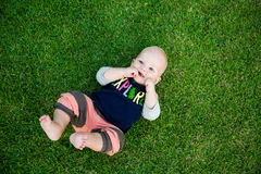 Happy adorable baby boy sitting on the grass and laughing in sum Stock Image