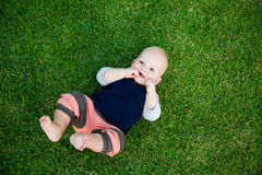 Happy adorable baby boy sitting on the grass. And laughing in summer day. Happy smile, 8 months old. Child in trendy and cute clothes Royalty Free Stock Image