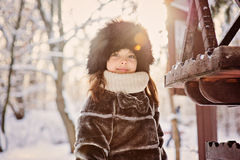 Happy adorable child girl in fur hat and coat near bird feeder on the walk in winter forest