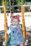 Happy adorable child girl on swing on playground near kindergarten Montessori on summer Stock Photo