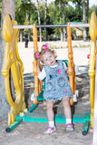 Happy adorable child girl on swing on playground near kindergarten Montessori on summer Royalty Free Stock Photo