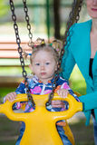 Happy adorable child girl on swing on playground near kindergarten Montessori Stock Image