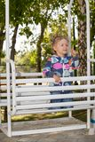 Happy adorable child girl on swing on playground near kindergarten Montessori Stock Photography