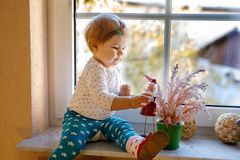 Happy adorable cute baby girl sitting near window and looking outside on snow on winter or spring day. Smiling child playing and looking interested and curious Royalty Free Stock Photos
