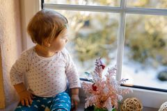 Happy adorable cute baby girl sitting near window and looking outside on snow on winter or spring day royalty free stock photography