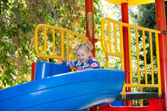 Happy adorable girl on children's slide on playground near kindergarten Montessori Stock Photo