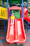 Happy adorable girl on children`s slide on playground near kindergarten Montessori on summer day Stock Photos