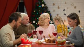 Happy adorable girl hugging grandparents, family having traditional Xmas dinner. Stock footage stock footage
