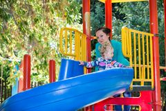 Happy adorable girl with mom on children's slide on playground near kindergarten Montessori Stock Photos