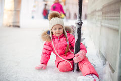 Happy adorable girl sitting on ice with skates Stock Images