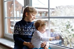 Happy adorable kid boy and cute baby girl sitting near window and looking outside on snow on Christmas day or morning. Smiling children, siblings, little Royalty Free Stock Photos
