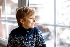 Happy adorable kid boy sitting near window and looking outside on snow on Christmas day or morning. stock images