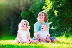 Happy adorable kids in the sunny garden. Three happy kids, brothers and sister, laughing teenager boy, little baby and a funny curly girl playing together with stock image