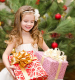 Happy adorable little girl with gift boxes Stock Photo