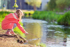 Happy adorable little girl playing near pond in sunny day Royalty Free Stock Photography