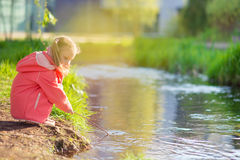 Happy adorable little girl playing near pond in sunny day Stock Photography