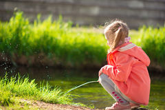 Happy adorable little girl playing near pond in sunny day Royalty Free Stock Photo