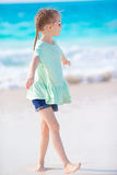 Happy adorable little girl walking on the white beach Royalty Free Stock Photo