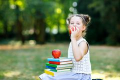 Happy adorable little kid girl reading book and holding different colorful books, apples and glasses on first day to royalty free stock photo
