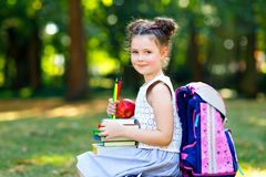 Happy adorable little kid girl reading book and holding different colorful books, apples and pencils on first day to. School or nursery. Back to school concept royalty free stock photos