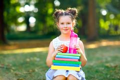 Happy adorable little kid girl reading book and holding different colorful books, apples and water bottle on first day. To school or nursery. Back to school royalty free stock image