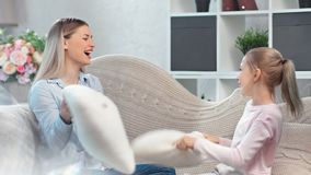 Happy adorable mother and smiling daughter fighting pillow having fun at cozy living room. Medium shot. Laughing family young woman cute girl playing relaxing stock video footage