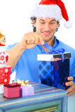 Happy Adult Caucasian Male Opening Gift. Happy young adult wearing christmas santa hat opening gift royalty free stock photos