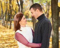 Happy adult couple embrace in autumn city park, trees with yellow leaves, bright sun and happy emotions, tenderness and feelings Royalty Free Stock Image