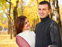 Happy adult couple embrace in autumn city park, trees with yellow leaves, bright sun and happy emotions, tenderness and feelings Royalty Free Stock Photography