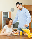 Happy adult couple having breakfast with juice Royalty Free Stock Photos