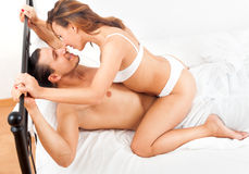 Happy adult couple having sex on bed in bedroom interior Royalty Free Stock Image