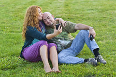 Happy adult couple man and woman sitting on grass with mobile Stock Photography
