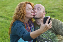 Happy adult couple sitting on grass sends kiss to phone Stock Photos