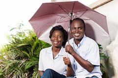 Happy adult couple sitting and protecting himself with an umbrella. Happy adult couple sitting and protecting himself with an umbrella near a flower stock images