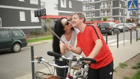 Happy Adult Couple Taking Selfie After Bicycle Riding. A Mab Holds Smartphone on a Stick. At This Moment The Girl Hugs. And Flirts with Him. HD, Summer, Outdoor stock video