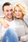 Happy adult couple using laptop at home Royalty Free Stock Images
