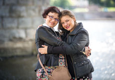 Happy adult daughter hugging with mother on riverbank Royalty Free Stock Photo