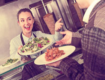 Happy adult  female worker serving customer. With smile at shawarma place Stock Images
