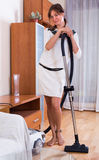 Happy adult girl hoovering and cleaning Royalty Free Stock Photos