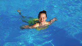 A happy and adult girl swims in the swimming pool to the side, the summer season stock footage