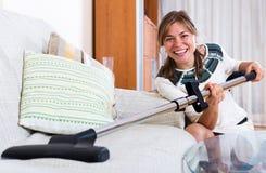 Happy adult girl vacuuming floor Royalty Free Stock Photography