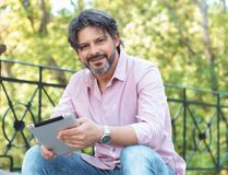 Happy adult handsome man sitting outdoors and tablet Royalty Free Stock Images