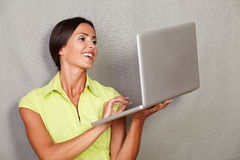 Happy adult lady smiling while using laptop Stock Images