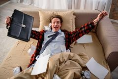 Jubilant man exulting on the sofa at home. Happy adult male lying in bed and rejoicing. He is looking at camera with triumphant glance. Free from work concept Stock Images