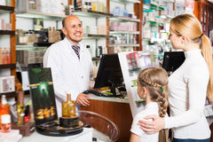 Happy adult male pharmacist helping customers. Happy adult male pharmacist wearing white coat standing next to shelves with medicine and helping customers Stock Images