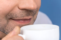 Happy adult man drinking coffee on blue. Stock Photos