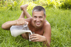 The happy adult man drinks fresh milk Stock Photo
