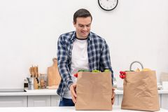 Happy adult man with grocery store paper bags. At kitchen stock photos