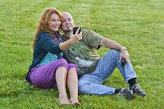 Happy adult man and woman sitting on grass with mobile phone Stock Image