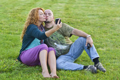 Happy adult man and woman sitting on grass with phone Royalty Free Stock Image